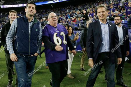 Former House Speaker Paul Ryan of Wisc., Gov. Larry Hogan, R-Md., and Gov. Gov. Bill Lee, R-Tenn., from left, walks on the turf before an NFL divisional playoff football game between the Baltimore Ravens and the Tennessee Titans, in Baltimore