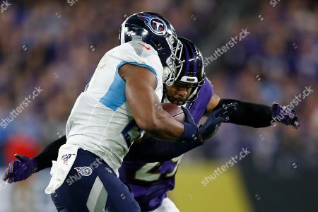 Tennessee Titans tight end Jonnu Smith (81) is wrapped up by Baltimore Ravens free safety Earl Thomas (29) during the first half an NFL divisional playoff football game, in Baltimore