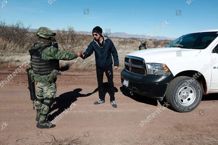 A National Guard soldier returns identification to a journalist at a military checkpoint near Bavispe, Sonora state, Mexico, where family members of the extended LeBaron family were ambushed by gunmen last year, one day before the expected arrival of Mexican President Andrés Manuel López Obrador, . The three women and six of their children, all U.S. citizens, were slaughtered and one of their cars burned here on Nov. 4, 2019