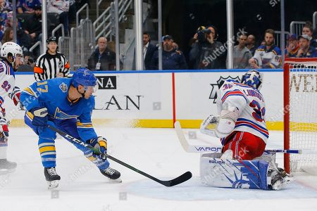 St. Louis Blues' Jaden Schwartz, left, scores a goal against New York Rangers goaltender Henrik Lundqvist, of Sweden, during the second period of an NHL hockey game, in St. Louis