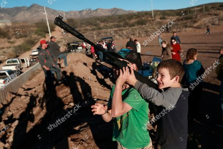 Boys point an unloaded gun at the sky as they play in La Mora, Sonora state, Mexico, one day before the expected arrival of Mexican President Andrés Manuel López Obrador, . Three women and six of their children from La Mora, all U.S. citizens from the extended LeBaron family, were slaughtered and their cars burned by gunmen in this area on Nov. 4, 2019