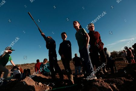 A boy points an unloaded gun at the sky on the sidelines of a ball game in La Mora, Sonora state, Mexico, one day before the expected arrival of Mexican President Andrés Manuel López Obrador, . Three women and six of their children from La Mora, all U.S. citizens from the extended LeBaron family, were slaughtered and their cars burned by gunmen in this area on Nov. 4, 2019