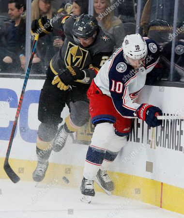 Vegas Golden Knights left wing William Carrier (28) checks Columbus Blue Jackets center Alexander Wennberg (10) into the boards during the second period of an NHL hockey game, in Las Vegas