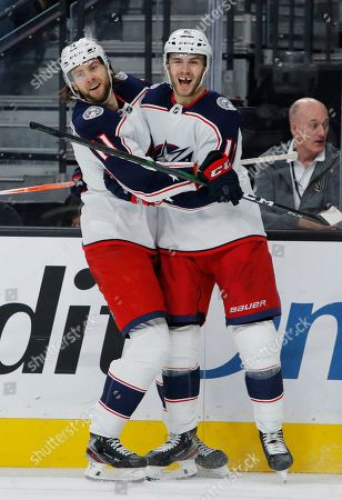 Columbus Blue Jackets' Kevin Stenlund, left, celebrates with Alexander Wennberg, right, who scored against the Vegas Golden Knights during the third period of an NHL hockey game, in Las Vegas