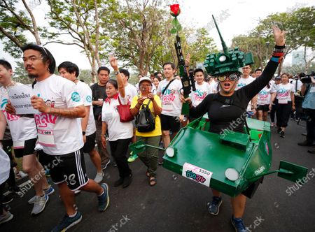 A Thai anti-government runner dressed up in a costume depicting a military tank holds a toy gun while flashing a three-finger salute during the 'Run Against Dictatorship', a political rally event at a public park in Bangkok, Thailand, 12 January 2020. Thousands of people took part in the morning jog anti-government rally event 'Run Against Dictatorship' dubbed in Thai as 'Run to Oust Uncle', a subtle reference to Thai Prime Minister Prayut Chan-o-cha, while a rival group held the 'Walk to Cheer Uncle' to support the government.