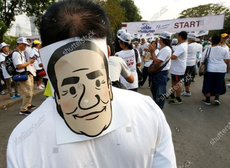 A supporter wears a mask of Thai Prime Minister Prayut Chan-o-cha (L) as they join the 'Dern Cheer Lung' or 'Walk for Prayut' event at Lumpini Park in Bangkok, Thailand, 12 January 2020. Thousand supporters gathered for the walking event organized to show support for Thai Prime Minister Prayut Chan-o-cha, and to demand that he remain prime minister of the country.