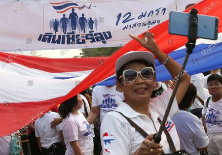 A supporter of Thai Prime Minister Prayut Chan-o-cha takes pictures as they participate in the 'Dern Cheer Lung' or 'Walk for Prayut' event at Lumpini Park in Bangkok, Thailand, 12 January 2020. Thousand supporters gathered for the walking event organized to show support for Thai Prime Minister Prayut Chan-o-cha, and to demand that he remain prime minister of the country.