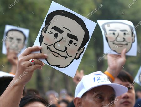 Stock Photo of Supporters cheer and hold masks of Thai Prime Minister Prayut Chan-o-cha as they participate in the 'Dern Cheer Lung' or 'Walk for Prayut' event at Lumpini Park in Bangkok, Thailand, 12 January 2020. Thousand supporters gathered for the walking event organized to show support for Thai Prime Minister Prayut Chan-o-cha, and to demand that he remain prime minister of the country.