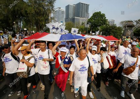 Supporters walk and carry a large Thai national flag as they participate in the 'Dern Cheer Lung' or 'Walk for Prayut' event at Lumpini Park in Bangkok, Thailand, 12 January 2020. Thousand supporters gathered for the walking event organized to show support for Thai Prime Minister Prayut Chan-o-cha, and to demand that he remain prime minister of the country.
