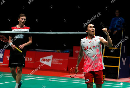 Japan's Kento Momota, left, celebrates after defeating Denmark's Viktor Axelsen during men single final of the Malaysia Masters in Kuala Lumpur, Malaysia