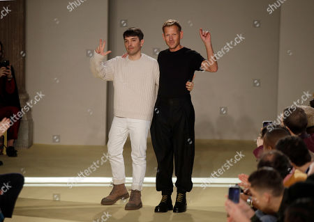 Creative director Paul Andrew, right, accept applause flanked by menswear designer Guillaume Meilland, at the conclusion of the the Salvatore Ferragamo men's Fall-Winter 2020/21 fashion show, that was presented during the fashion week, in Milan, Italy