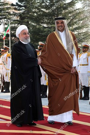 In this photo released by official website of the Office of the Iranian Presidency, Emir of Qatar Sheikh Tamim bin Hamad Al Thani, right, and Iranian President Hassan Rouhani shake hands during an official welcome ceremony in Tehran, Iran