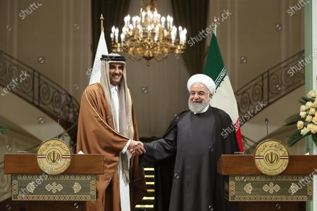 Stock Picture of A handout photo made available by Iran's Presidential Office shows Iranian President Hassan Rouhani (R) and Emir of Qatar Sheikh Tamim bin Hamad al-Thani (L) shaking hands during a joint press conference following their meeting in Tehran, Iran, 12 January 2020. According to reports, Sheikh Tamim is visiting Tehran amid regional tension.