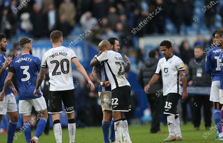 Andre Ayew of Swansea City and Lee Tomlin of Cardiff City embrace at the end of the match