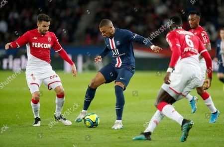 PSG's Kylian Mbappe, center, is challenged by Monaco's Tiemoue Bakayoko, right, and Monaco's Cesc Fabregas, left, during the French League One soccer match between Paris-Saint-Germain and Monaco at the Parc des Princes stadium in Paris