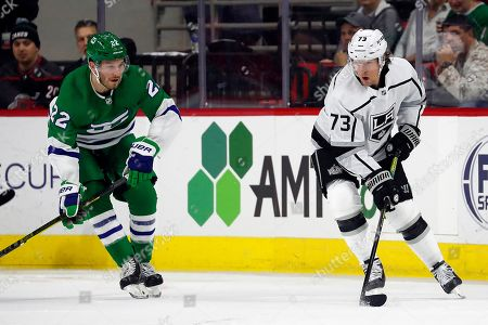 Tyler Toffoli, Brett Pesce. Los Angeles Kings' Tyler Toffoli (73) protects the puck from Carolina Hurricanes' Brett Pesce (22) during the second period of an NHL hockey game in Raleigh, N.C