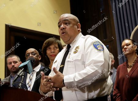 Michael Harrison, center, acting commissioner of the Baltimore Police Department, speaks at an introductory news conference in Baltimore. Authorities say 12 people have been shot, five of them fatally, in eight separate weekend shootings in Baltimore