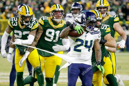 Green Bay Packers' Jaire Alexander (23) and others try to stop Seattle Seahawks' Marshawn Lynch (24) during the first half of an NFL divisional playoff football game, in Green Bay, Wis