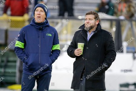 Seattle Seahawks head coach Pete Carroll and general manager John Schneider watch warm ups before an NFL divisional playoff football game against the Green Bay Packers, in Green Bay, Wis