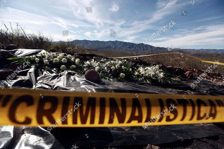 Stock Picture of Flowers placed by relatives remain where one of the cars belonging to the extended LeBaron family was ambushed by gunmen last year near Bavispe, Sonora state, Mexico, . Lopez Obrador said Sunday there is an agreement to establish a monument will be put up to memorialize nine U.S.-Mexican dual citizens ambushed and slain last year by drug gang assassins along a remote road near New Mexico