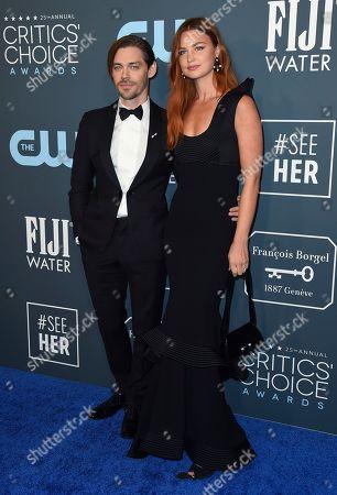 Tom Payne, Jennifer Akerman. Tom Payne, left, and Jennifer Akerman arrive at the 25th annual Critics' Choice Awards, at the Barker Hangar in Santa Monica, Calif