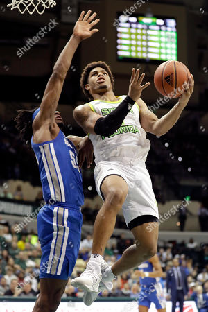 Precious Achiuwa, David Collins. South Florida guard David Collins (0) goes to the basket over Memphis forward Precious Achiuwa (55) during the second half of an NCAA college basketball game, in Tampa, Fla