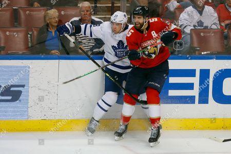 Travis Dermott, Aaron Ekblad. Florida Panthers defenseman Aaron Ekblad (5) knocks Toronto Maple Leafs defenseman Travis Dermott (23) into the boards during the third period of an NHL hockey game, in Sunrise, Fla. The Panthers defeated the Maple Leafs 8-4