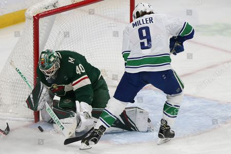 J.T. Miller, Devan Dubnyk. Vancouver Canucks' J.T. Miller tries to score a goal as Minnesota Wild's goalie Devan Dubnyk blocks the net in the first period of an NHL hockey game, in St. Paul, Minn. Vancouver won 4-1