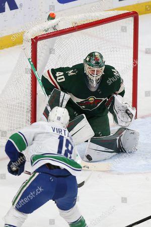 Devan Dubnyk, Jake Virtanen. Minnesota Wild's goalie Devan Dubnyk blocks a shot by Vancouver Canucks' Jake Virtanen in the first period of an NHL hockey game, in St. Paul, Minn. Vancouver won 4-1