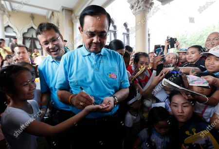 Thailand's Prime Minister Prayut Chan-o-cha signs autographs during the Children's Day celebration at Government House in Bangkok.