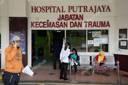 People wait outside the Putrajaya hospital in Putrajaya, Malaysia, . World top badminton player Kento Momota from Japan, was injured during a car accident in Malaysia early Monday and he is receiving a treatment at the hospital according to health minister