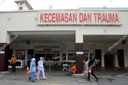 People walk outside the Putrajaya hospital in Putrajaya, Malaysia, . World top badminton player Kento Momota from Japan, was injured during a car accident in Malaysia early Monday and he is receiving a treatment at the hospital according to health minister