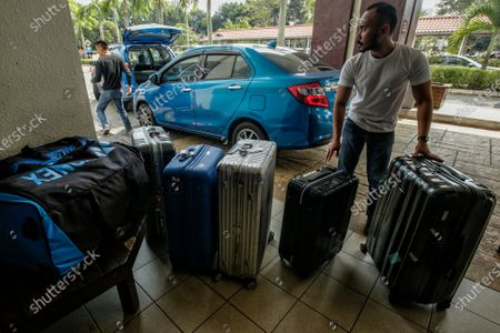 A man unloads the luggage of the Japanese badminton team at a hospital in Putrajaya, Malaysia, 13 January 2020. According to media reports, world number one badminton player, Japanese Kento Momota, suffered a broken nose and received stitches at his lips following a deadly crash between a van and a truck in Kuala Lumpur on 13 January.