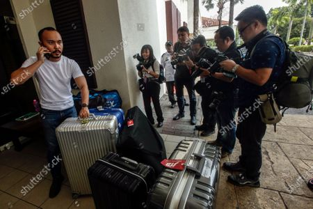 Members of the press take photos as a man unloads the luggage of the Japanese badminton team at a hospital in Putrajaya, Malaysia, 13 January 2020. According to media reports, world number one badminton player, Japanese Kento Momota, suffered a broken nose and received stitches at his lips following a deadly crash between a van and a truck in Kuala Lumpur on 13 January.