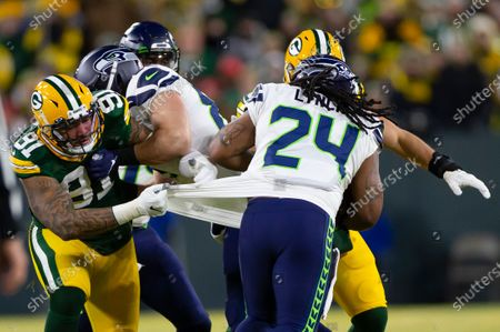 Green Bay Packers outside linebacker Preston Smith #91 grabs the shirt of Seattle Seahawks running back Marshawn Lynch #24 while attempting to make a tackle during the NFL Football game between the Seattle Seahawks and the Green Bay Packers at Lambeau Field in Green Bay, WI. Packers defeated the Seahawks 28-23