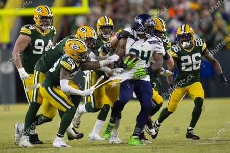 Green Bay Packers cornerback Jaire Alexander #23 rips the shirt of Seattle Seahawks running back Marshawn Lynch #24 while a host of Packers make the tackle during the NFL Football game between the Seattle Seahawks and the Green Bay Packers at Lambeau Field in Green Bay, WI. Packers defeated the Seahawks 28-23