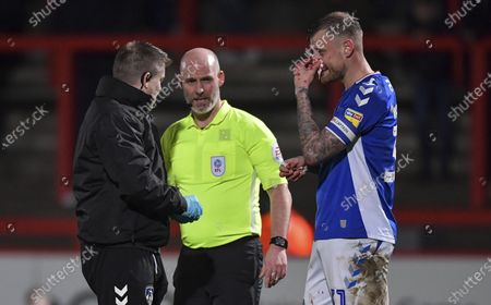 David Wheater of Oldham Athletic receives treatment for a bloody nose