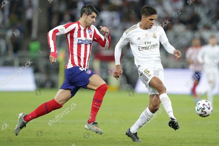 Atletico Madrid's Alvaro Morata, left, fights for the ball with Real Madrid's Raphael Varane during the Spanish Super Cup Final soccer match between Real Madrid and Atletico Madrid at King Abdullah stadium in Jiddah, Saudi Arabia