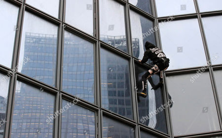 """French urban climber Alain Robert, well known as """"Spiderman"""", climbs up the Total tower in the Paris business district of La Defense, in support of the transport strikes"""