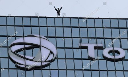 """French urban climber Alain Robert, well known as """"Spiderman"""", raises his arms as he finished to climb the Total tower in the Paris business district of La Defense, in support of the transport strikes"""