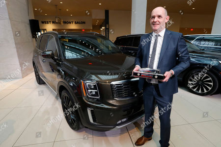 Michael Cole, president of Kia North America, holds the trophy after the Kia Telluride was awarded North American Sport Utility of the Year in Detroit, . The new mid-engine Chevrolet Corvette was named the North American Car of the Year and the Jeep Gladiator won the Truck of the Year award