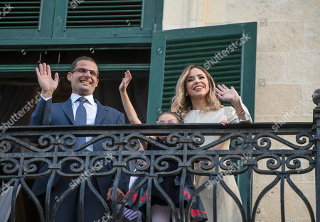 The new Prime Minister of Malta Robert Abela waves to the crowd from the President of Malta's balcony after the swearing in ceremony, together with his wife Lydia Abela and his daughter Giorgia Mae, . Abela is replacing Joseph Muscat after weeks of protests demanding accountability in the investigation of the car bomb slaying of an anti-corruption journalist who targeted his government