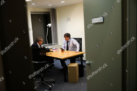 Catalonia's former regional president Carles Puigdemont, right, talks to his advisor in his bare new office at the European Parliament in Strasbourg, eastern France,. Puigdemont attended his first session as a member of the European Parliament despite facing an arrest warrant against him in Spain