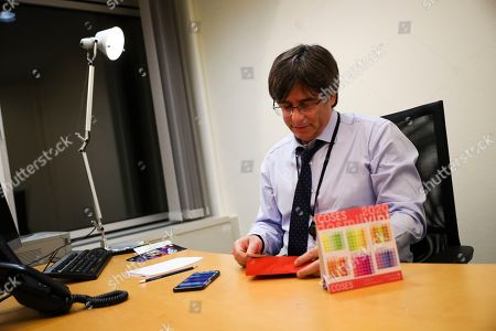 Catalonia's former regional president Carles Puigdemont opens an envelope in his bare new office at the European Parliament in Strasbourg, eastern France,. Puigdemont attended his first session as a member of the European Parliament despite facing an arrest warrant against him in Spain