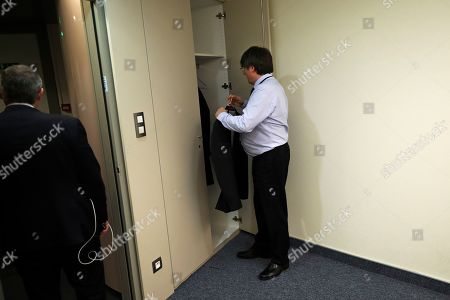 Catalonia's former regional president Carles Puigdemont hangs his jacket in his bare new office at the European Parliament in Strasbourg, eastern France,. Puigdemont attended his first session as a member of the European Parliament despite facing an arrest warrant against him in Spain