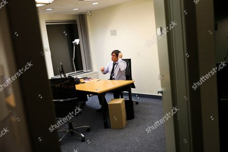 Catalonia's former regional president Carles Puigdemont talks to his advisor in his bare new office at the European Parliament in Strasbourg, eastern France,. Puigdemont attended his first session as a member of the European Parliament despite facing an arrest warrant against him in Spain