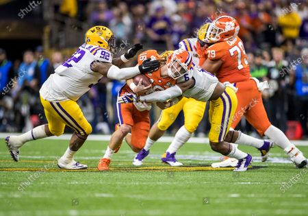 Stock Image of LSU linebacker Jacob Phillips (6) and LSU defensive lineman Neil Farrell Jr. (92) make the tackle on Clemson quarterback Trevor Lawrence (16) during College Football Playoff National Championship game action between the Clemson Tigers and the LSU Tigers at Mercedes-Benz Superdome in New Orleans, Louisiana. LSU defeated Clemson 42-25
