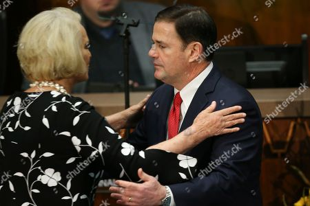 Arizona Republican Gov. Doug Ducey, right, hugs Cindy McCain, left, wife of former Arizona Sen. John McCain, after delivering his State of the State address on the opening day of the legislative session at the Capitol, in Phoenix