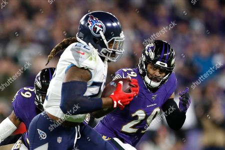 Baltimore Ravens free safety Earl Thomas, right, eyes Tennessee Titans running back Derrick Henry as he runs for yardage during the firs half of an NFL divisional playoff football game, in Baltimore. The Titans won 28-12
