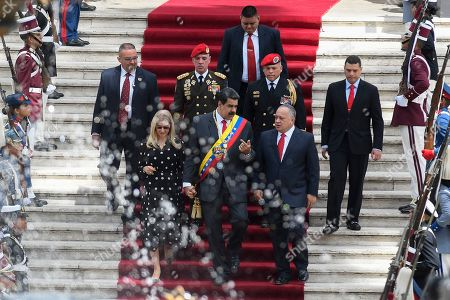 Seen through a water fountain, Venezuela's President Nicolas Maduro, center, first lady Cilia Flores, left, and Constituent Assembly President Diosdado Cabello arrive to the Constituent Assembly where Maduro will give his annual address to the nation on the grounds of the National Assembly in Caracas, Venezuela